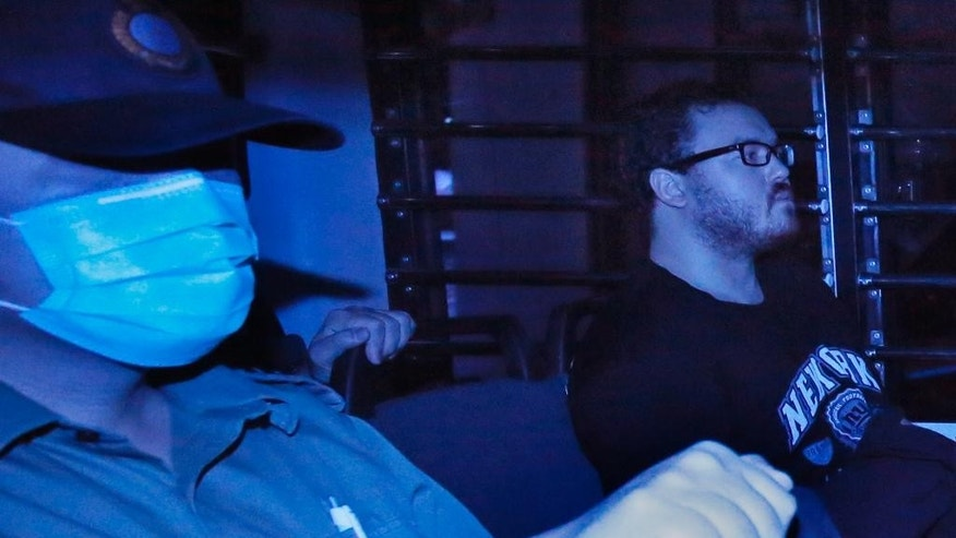 In this photo taken through tinted glass, Rurik George Caton Jutting, right, a 29-years-old  British banker, is escorted by Correctional Services officers in a prison bus arriving at a court in Hong Kong Monday, Nov. 10, 2014. The British banker will undergo a psychiatric assessment to determine whether he is fit to enter a plea in his Hong Kong trial over the deaths of two Indonesian women he is suspected of killing.   (AP Photo/Vincent Yu)