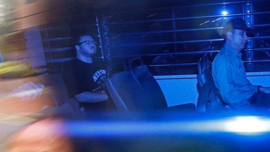 In this photo taken through tinted glass, Rurik George Caton Jutting, second right, a 29-years-old British banker, is escorted by Correctional Services officers in a prison bus arriving at a court in Hong Kong Monday, Nov. 10, 2014. The British banker will undergo a psychiatric assessment to determine whether he is fit to enter a plea in his Hong Kong trial over the deaths of two Indonesian women he is suspected of killing.   (AP Photo/Vincent Yu)