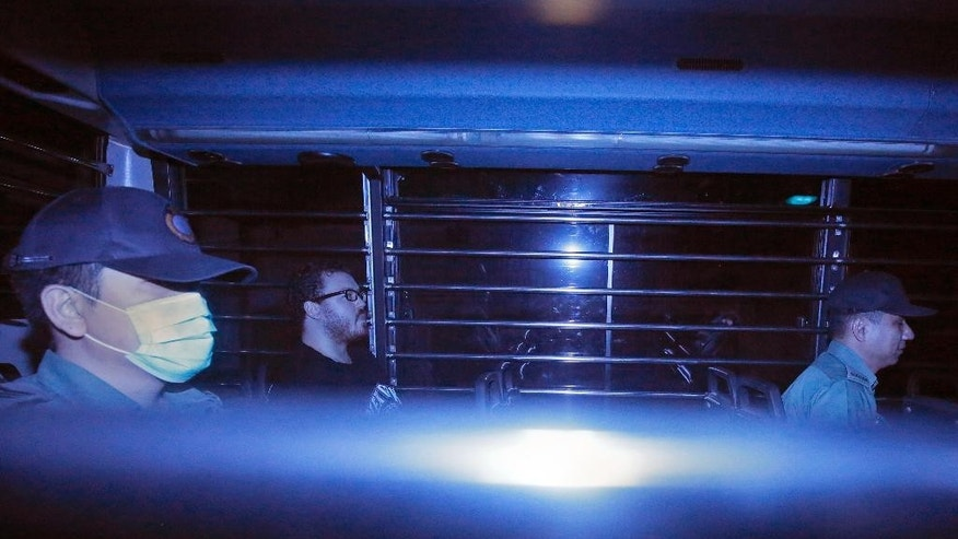 In this photo taken through tinted glass, Rurik George Caton Jutting, second left, a 29-years-old British banker, is escorted by Correctional Services officers in a prison bus arriving at a court in Hong Kong Monday, Nov. 10, 2014. The British banker will undergo a psychiatric assessment to determine whether he is fit to enter a plea in his Hong Kong trial over the deaths of two Indonesian women he is suspected of killing.   (AP Photo/Vincent Yu)