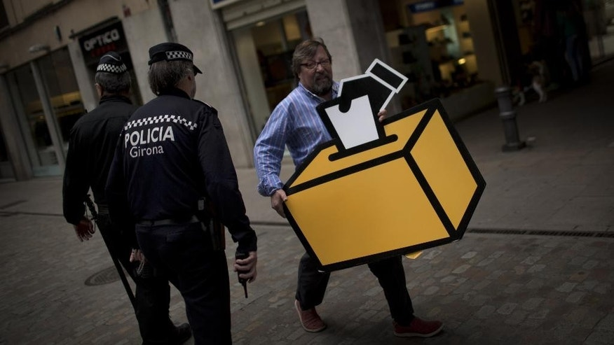 Businessman Emilio Busquets walks past two police officers patrolling the street, as he holds a drawing of a ballot box to decorate his shop ahead of voting on an informal poll, scheduled for next Sunday, in Girona, Spain, on Saturday Nov. 8, 2014. The pro-independence regional government of Catalonia stages a symbolic poll on secession in a show of determination and defiance after the Constitutional Court suspended its plans to hold an official independence referendum following a legal challenge by the Spanish government. (AP Photo/Emilio Morenatti)