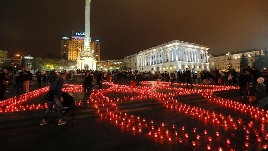 """Lit candles in the shape of the coat of arms of Ukraine are set up in Independence Square in Kiev, Ukraine, during a patriotic event - """"Ukraine - it's me!"""", Saturday Nov. 8, 2014. (AP Photo/Sergei Chuzavkov)"""