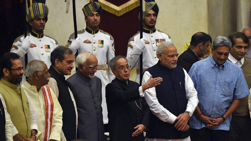 Indian President Pranab Mukherjee, center, gestures as he poses for photographs with Prime Minister Narendra Modi, third right, Vice President Hamid Ansari, fourth left and the newly sworn in ministers at the presidential palace in New Delhi, India, Sunday, Nov.9, 2014.Modi expanded his council of ministers Sunday in a bid to boost the government's agenda and kick-start the economy. (AP Photo/Prakash Singh, Pool)