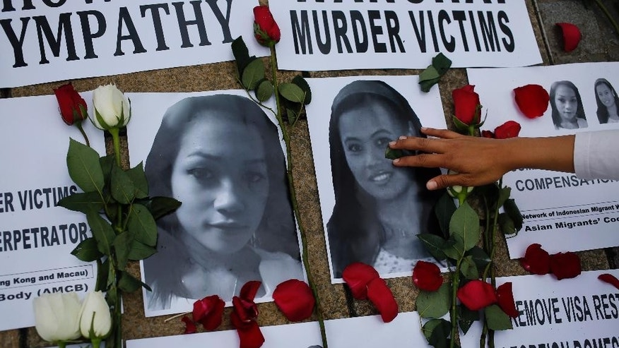 An Indonesian domestic worker puts flowers on pictures of Sumarti Ningsih, left, and Seneng Mujiasih during a vigil to express their solidarity and to demand justice at a park in Hong Kong Sunday, Nov. 9, 2014. Both Ningsih and Mujiasih are former domestic workers in their 20s who were found stabbed to death in the luxury apartment of British investment banker Rurik George Caton Jutting. (AP Photo/Vincent Yu)
