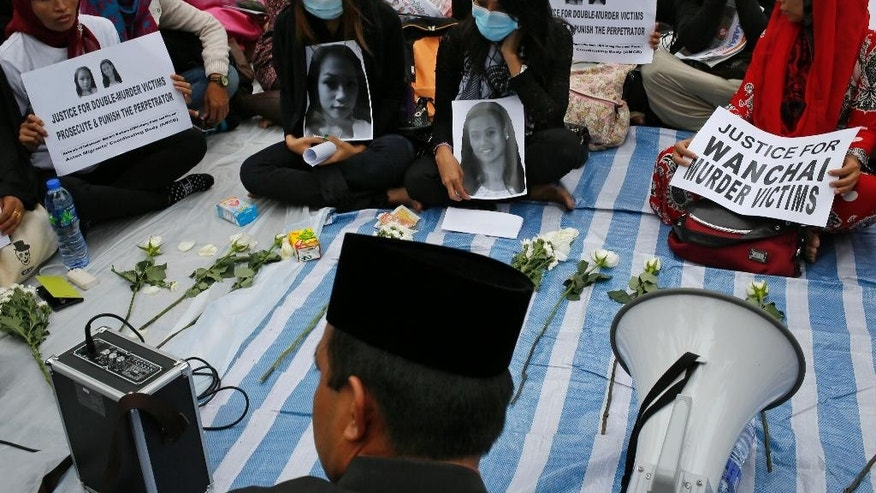 Jumiati, center left, cousin of Sumarti Ningsih and Susiati, center right, friend of  Seneng Mujiasih, attend a vigil to express her solidarity and to demand justice for Ningsih and Mujiasih at a park in Hong Kong Sunday, Nov. 9, 2014. Both Ningsih and Mujiasih are former domestic workers in their 20s who were found stabbed to death in the luxury apartment of British investment banker Rurik George Caton Jutting. (AP Photo/Vincent Yu)