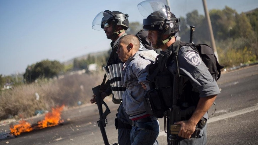 Nov. 9, 2014: Israeli riot police officers arrest an Israeli Arab during a protest over the fatal shooting of a 22-year-old Arab Israeli who appeared in video footage to be retreating from police, in the Arab village of Kfar Kana, northern Israel. (AP)