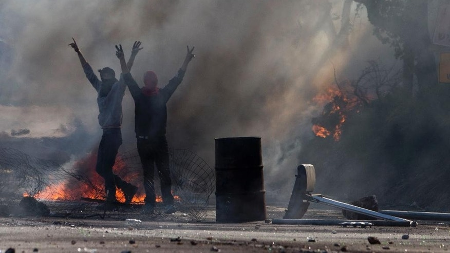Nov. 9, 2014: Israeli Arabs flash victory signs during a protest over the fatal shooting of a 22-year-old Arab Israeli who appeared in video footage to be retreating from police, in the Arab village of Kfar Kana, northern Israel. (AP)