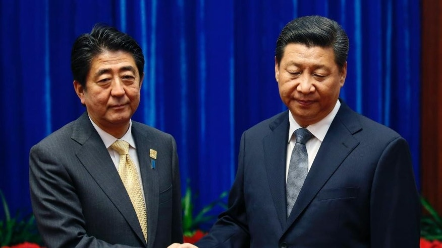 China's President Xi Jinping, right,  shakes hands with Japan's Prime Minister Shinzo Abe, during their meeting at the Great Hall of the People, on the sidelines of the Asia Pacific Economic Cooperation (APEC) meetings, in Beijing, Monday, Nov. 10, 2014. President Xi and Prime Minister Abe held an ice-breaking meeting Monday on the sidelines of an Asia-Pacific conference in Beijing, following more than two years of deep tensions over an island dispute.  (AP Photo/Kim Kyung-Hoon, Pool)