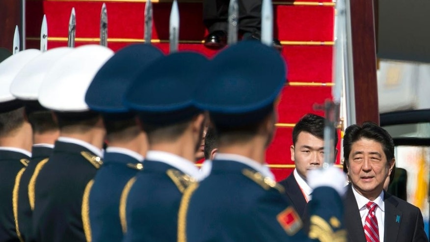Japanese Prime Minister Shinzo Abe passes by a Chinese guard of honor as he arrives ahead of the Asia-Pacific Economic Cooperation (APEC) Economic Leaders' Week at the airport in Beijing Sunday, Nov. 9, 2014. (AP Photo/Ng Han Guan)