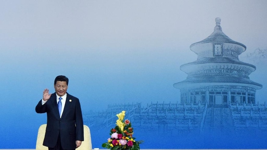China's President Xi Jinping waves as he stands up to give a speech to open the APEC CEO Summit as part of the Asia-Pacific Economic Cooperation (APEC) Summit at the China National Convention Center in Beijing, Sunday, Nov. 9, 2014. (AP Photo/Wang Zhao, Pool)