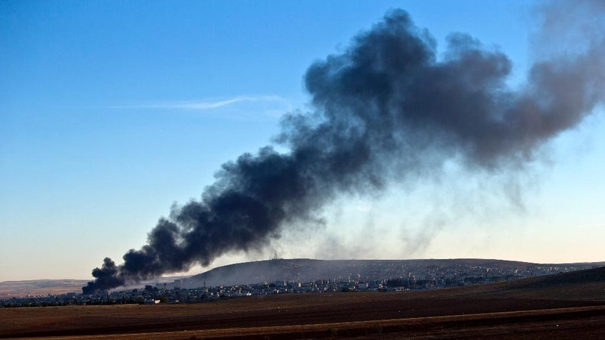 Smoke rises from an Islamic State position in eastern Kobani, after an airstrike by the US led coalition, seen from a hilltop outside Suruc, on the Turkey-Syria border Saturday, Nov. 8, 2014. Kobani, also known as Ayn Arab, and its surrounding areas, has been under assault by extremists of the Islamic State group since mid-September and is being defended by Kurdish fighters. (AP Photo/Vadim Ghirda)
