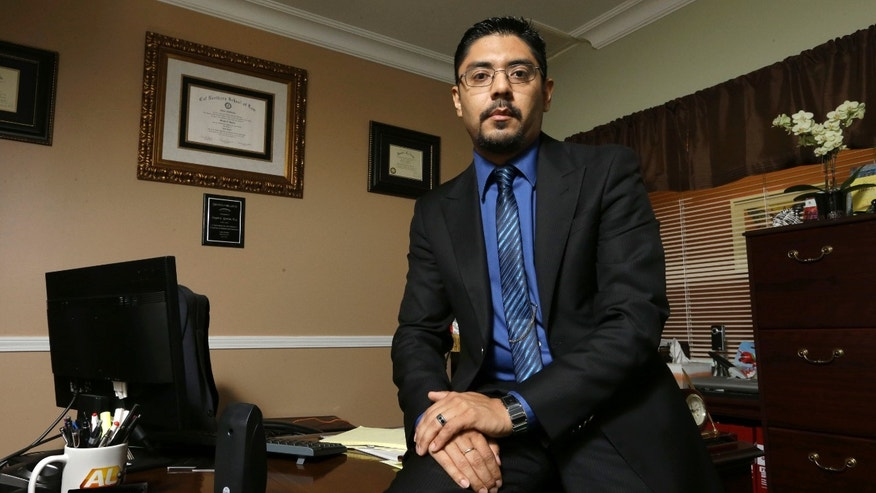 In this Oct. 30, 2014 photo, civil litigation lawyer Sergio Garcia poses in his office in Chico, Calif. Garcia, 37, a native of Mexico, won his license to practice law after a bruising five-year legal and political battle that included a ruling in January from the California Supreme Court. It came after Gov. Jerry Brown signed a specially crafted bill passed by the Legislature to let Garcia practice law. (AP Photo/Rich Pedroncelli)