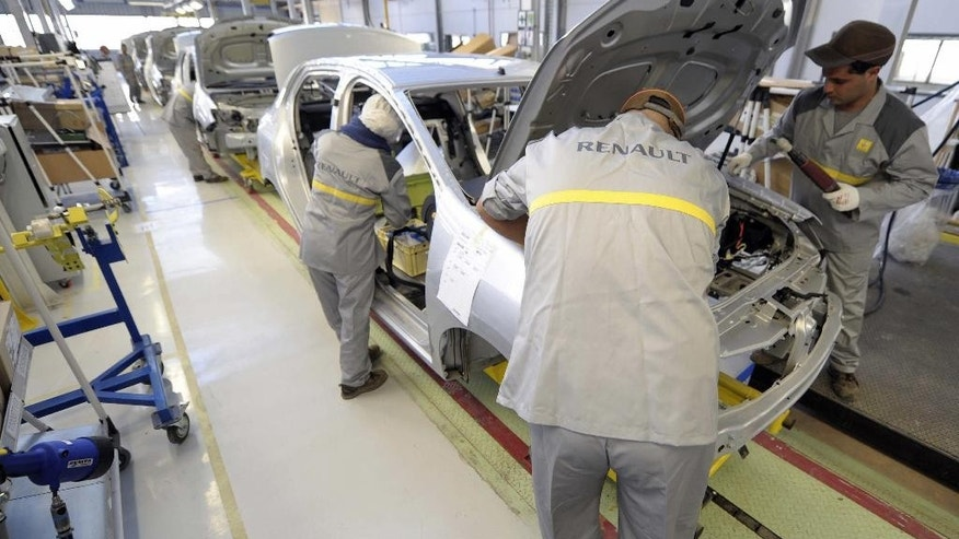 Employees work at the assembly line in the new Renault plant in Oran, western Algeria, Monday, Nov.10, 2014. The plant has been inaugurated Monday and is due to produce the Renault Symbol especially for the Algerian domestic market. The first new Renault car rolled off the assembly lines on Monday. (AP Photo/Sidali Djarboub)