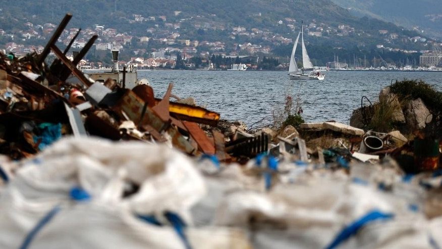 In this photo taken Tuesday, Nov. 4, 2014, a boat sails near a pile of jumbo bags filled with hazardous grit in an shipyard in Bijela, Montenegro. Montenegro takes pride in its majestic Adriatic coastline and towering mountains rising from the sea, lined with rivers, streams and lakes. But the so-called Balkan Wild Beauty also faces an ugly problem of waste disposal that is threatening both its natural wonders and lucrative tourism industry. (AP Photo/Darko Vojinovic)