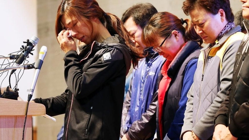Relatives of the nine missing passengers of the sunken ferry Sewol cry during a news conference at a gym on South Korea's southwestern island of Jindo, where they have been staying at since the April 16 sinking of ferry Sewol, in Jindo, South Korea, Tuesday, Nov. 11, 2014. A South Korean court on Tuesday handed a 36-year prison sentence to the captain of a sunken ferry, saying he was professionally negligent and abandoned his passengers during the disaster in April that killed more than 300 people. (AP Photo/Yonhap, Park Chul-hong) KOREA OUT
