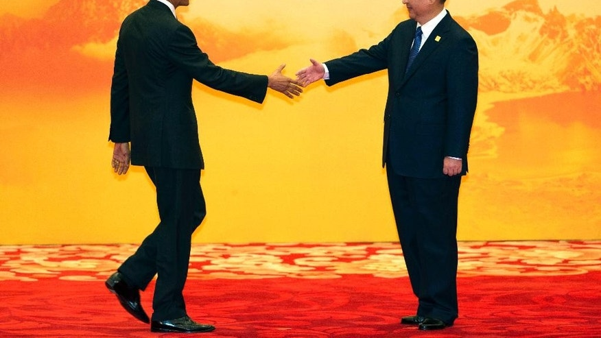 U.S.President Barack Obama, left, shakes hands with Chinese President Xi Jinping during a welcome ceremony for the Asia-Pacific Economic Cooperation (APEC) summit at the International Convention Center in Yanqi Lake, Beijing, China Tuesday, Nov. 11, 2014. (AP Photo/Ng Han Guan)