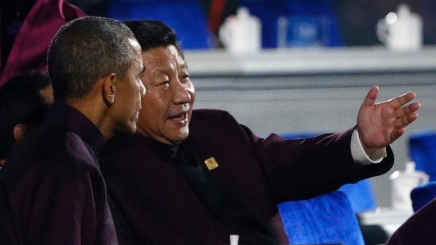 U.S. President Barack Obama, left, chats with Chinese President Xi Jinping as they prepare to watch a fireworks show after a welcome banquet for the Asia Pacific Economic Cooperation (APEC) summit in Beijing, China Monday, Nov. 10, 2014. (AP Photo) CHINA OUT