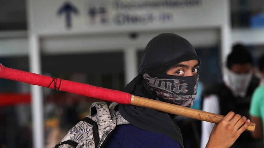 A masked student during a protest at the Acapulco airport in Mexico, Monday, Nov. 10, 2014.