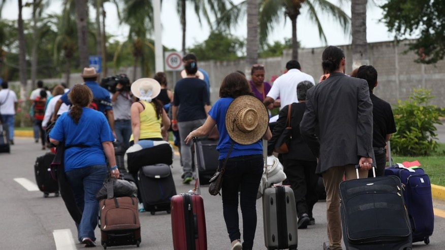 Travelers walk to their terminal due to students protesting the disappearance, and probable murder, of 43 students in the state of Guerrero, at the airport in Acapulco, Mexico, Monday, Nov. 10, 2014. Supporters of the missing students, refusing to believe they are dead, have kept up the protests that have blocked major highways and set government buildings ablaze in recent weeks. The travelers eventually left the airport, missing their flights. (AP Photo/Marco Ugarte)