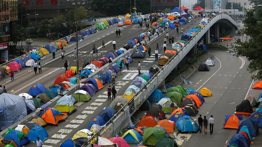 Tents set up by pro-democracy protesters are seen in an occupied area outside the government headquarters in Hong Kong's Admiralty district in Hong Kong Tuesday, Nov. 11, 2014. Pro-democracy protesters camped out on main streets in Hong Kong for more than six weeks face arrest after a court authorized police to help bailiffs clear them from occupation sites, a senior government official warned Tuesday. (AP Photo/Vincent Yu)