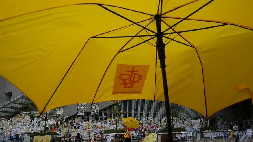 A man walks past a yellow umbrella which set up by pro-democracy protesters are seen in an occupied area outside government headquarters in Hong Kong's Admiralty district in Hong Kong Tuesday, Nov. 11, 2014. Pro-democracy protesters camped out on main streets in Hong Kong for more than six weeks face arrest after a court authorized police to help bailiffs clear them from occupation sites, a senior government official warned Tuesday. (AP Photo/Vincent Yu)