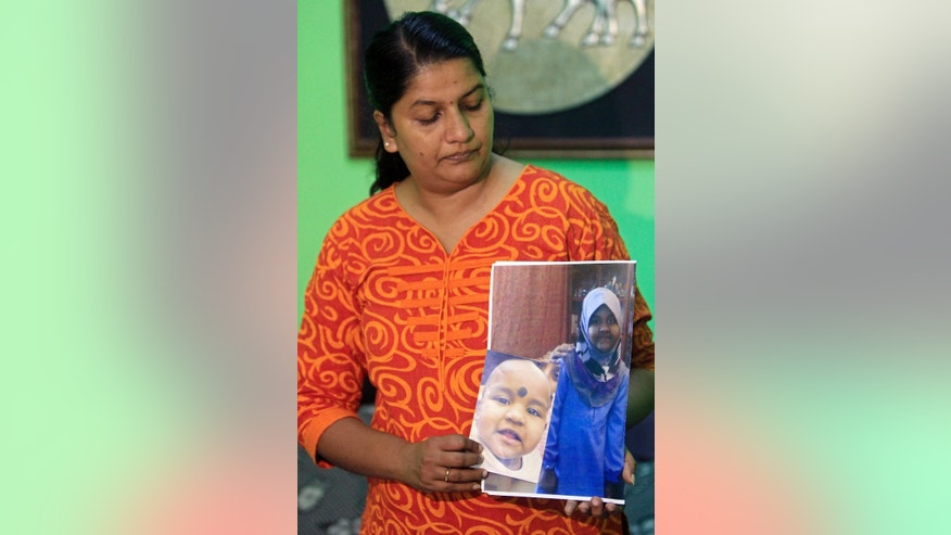 In this Oct. 16, 2014 photo, M. Indira Gandhi shows photos of her youngest daughter Prasana Diksa during an interview at her house in Ipoh, Perak state, Malaysia. Gandhi has just fed her youngest child and put her to sleep when her husband came home. He tried again to persuade her to convert to Islam but she held on to her Hindu faith, sparking a big row. All of a sudden, without any warning, he grabbed their 11-month-old baby and fled on his motorbike, five years ago. Gandhi hasn't seen her child since, even though a Malaysian civil court awarded her custody. Her husband - who converted to Islam shortly before taking his daughter away - won custody in an Islamic court. (AP Photo/Lai Seng Sin)