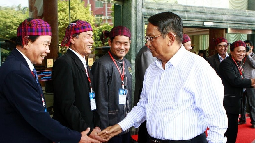 FILE - In this March 8, 2012 file photo, Aung Thaung, right, leader of Myanmar's government peace committee, shakes hands with a member of the Kachin Independence Organization during a signing ceremony of a peace agreement between the two sides, at Jin Cheng hotel in China's Shwe-Li town on the China-Myanmar border. The Myanmar Parliament has denounced a U.S. move to blacklist ruling party lawmaker Aung Thaung and says the decision could adversely affect bilateral relations. The announcement on Monday, Nov. 10, 2014, said the decision by the U.S. Treasury Department to blacklist Aung Thaung tarnishes the dignity of the lawmakers and parliamentary committees, one of which he leads. (AP Photo/Khin Maung Win, File)