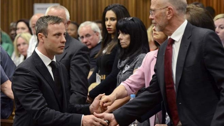 Oct. 21, 2014: Oscar Pistorius, left, greets his uncle Arnold Pistorius, right, and other family members as he is led down to the cells of the court in Pretoria.