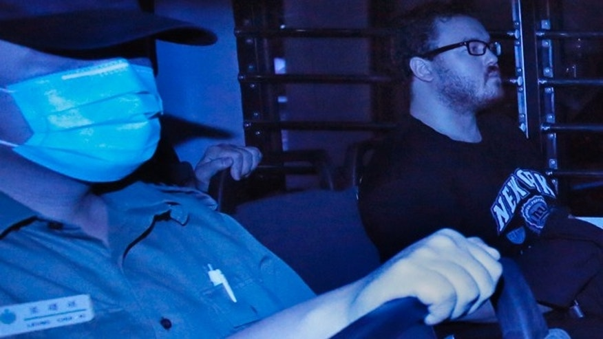 November 10, 2914: In this photo taken through tinted glass, Rurik George Caton Jutting, right, a 29-year-old British banker, is escorted by Correctional Services officers in a prison bus arriving at a court in Hong Kong. (AP Photo/Vincent Yu)
