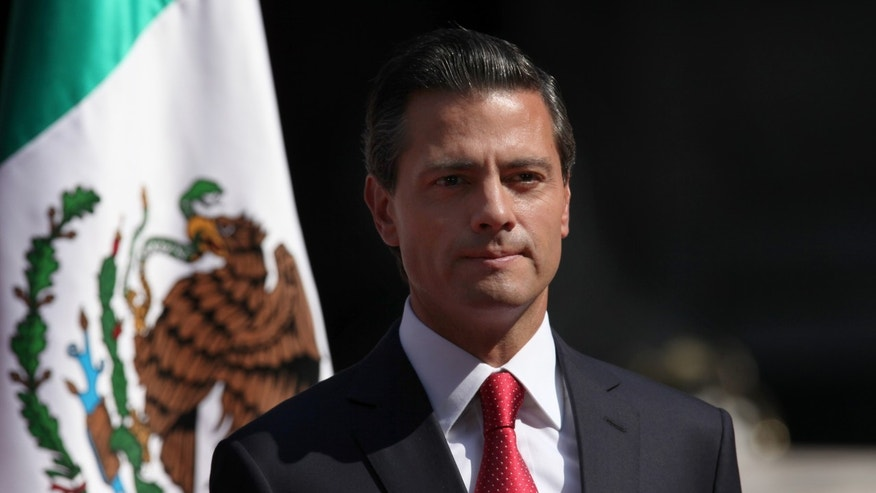 FILE - In this Nov. 3, 2014, file photo, Mexico's President Enrique Pena Nieto stands at attention as the national anthem of the UK and Mexico is played during an official visit by Britain's Prince Charles and his wife Camilla Duchess of Cornwall, at the National Palace in Mexico City. According to a report by a leading Mexican journalist, the private home of President Pena Nieto was built and is registered under the name of a company connected to a controversial high-speed rail contract that he abruptly canceled last week. The article did not specify what laws if any are broken by the president using a house registered under another name. (AP Photo/Marco Ugarte, File)