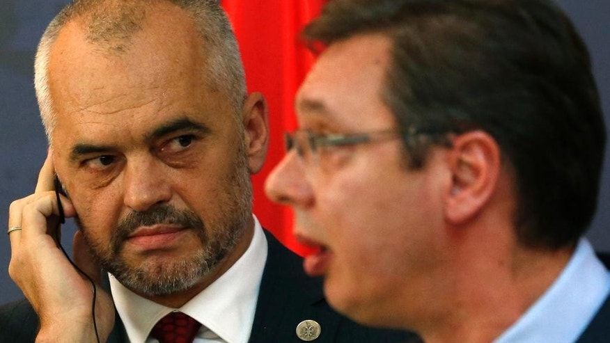 Albanian Prime Minister Edi Rama, left, listens his Serbian counterpart Aleksandar Vucic during a news conference in Belgrade, Serbia, Monday, Nov. 10, 2014. Rama arrived on a two-day official visit to Serbia the first by an Albanian leader in 68 years. (AP Photo/Darko Vojinovic)