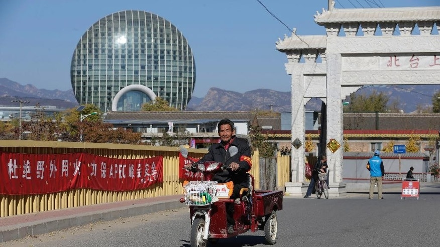 """In this Sunday, Nov. 9, 2014 photo, a man rides on a tricycle past banners with the words """"Ensure APEC summit's safety, open burning is prohibited"""" on display at a main road entrance to the Upper Beitai, the village closest to the venue for the upcoming Asia-Pacific Economic Cooperation (APEC) summit, in the Huairou district of Beijing, China Sunday, Nov. 9, 2014. The streets are tidier and new heating sources are on the way, but for now the nights are freezing for rural residents near the Beijing summit venue where authorities have banned wood fires to curb pollution. (AP Photo/Andy Wong)"""