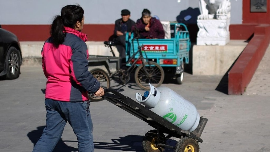 In this Sunday, Nov. 9, 2014 photo, a woman pushes a natural gas cylinder past an elderly couple taking a rest in the Upper Beitai, the village closest to the venue for the upcoming Asia-Pacific Economic Cooperation (APEC) summit, in the Huairou district of Beijing, China. The streets are tidier and new heating sources are on the way, but for now the nights are freezing for rural residents near the Beijing summit venue where authorities have banned wood fires to curb pollution. (AP Photo/Andy Wong)