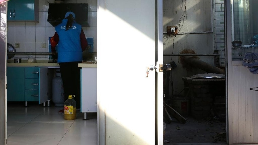 In this Sunday, Nov. 9, 2014 photo, a woman installs a natural gas cooker in her kitchen next to a room where she uses wood fires to cook in the past at the Upper Beitai, the village closest to the venue for the upcoming Asia-Pacific Economic Cooperation (APEC) summit, in the Huairou district of Beijing, China. The streets are tidier and new heating sources are on the way, but for now the nights are freezing for rural residents near the Beijing summit venue where authorities have banned wood fires to curb pollution. (AP Photo/Andy Wong)
