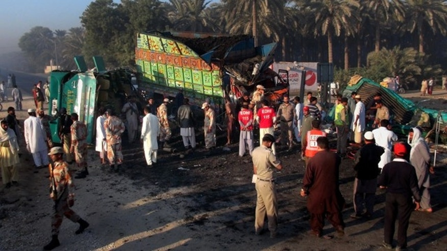 November 11, 2014: Pakistan paramilitary soldiers and rescue workers gather at the site of a collision between a bus and a truck in Khairpur district. (AP Photo/Pervez Khan)