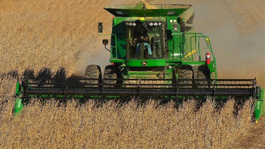 FILE - In this Tuesday, Oct. 21, 2014 file photo, a central Illinois farmer uses a John Deere combine to harvest his soybean field in Loami, Ill. Global growth is the buzzword for the Nov. 15-16, 2014 summit of leaders from the 20 biggest industrialized and developing economies in Brisbane, Australia, and there is pressure on the delegates to deliver on an ambitious plan to boost the world's GDP by more than $2 trillion. (AP Photo/Seth Perlman, File)