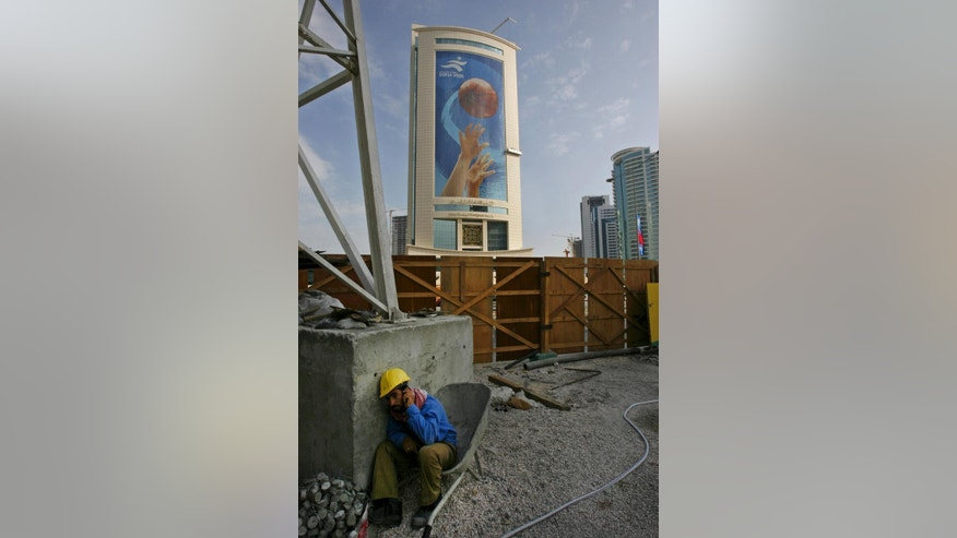 FILE - In this Nov. 30, 2006 file photo, a construction worker takes time off to call a friend in the backdrop of a large advertisement of the 15th Asian Games in Doha, Qatar. Amnesty International said Wednesday, Nov. 12, 2014, that 2022 World Cup host nation Qatar is lagging behind on addressing concerns about the abuse of migrant workers six months after it laid out plans for labor reforms. Like other energy-rich Gulf nations, Qatar relies heavily on migrant workers drawn mainly from South Asia to build its roads, skyscrapers and stadiums. (AP Photo/Saurabh Das-file)