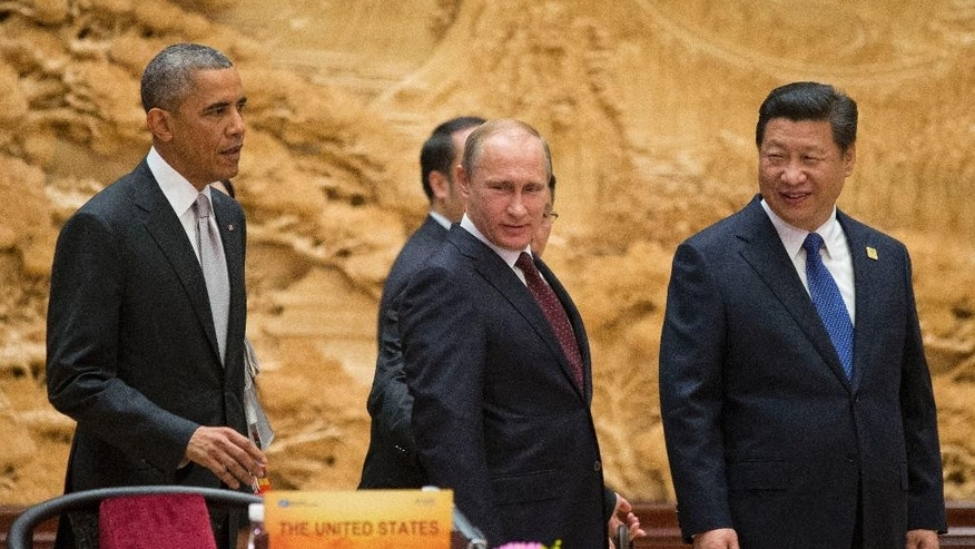 U.S. President Barack Obama, left,  Chinese President Xi Jinping, right, and Russian President Vladimir Putin, center, arrive at the the Asia-Pacific Economic Cooperation (APEC) Summit plenary session at the International Convention Center, Yanqi, Tuesday, Nov. 11, 2014 in Beijing. (AP Photo/Pablo Martinez Monsivais, Pool)