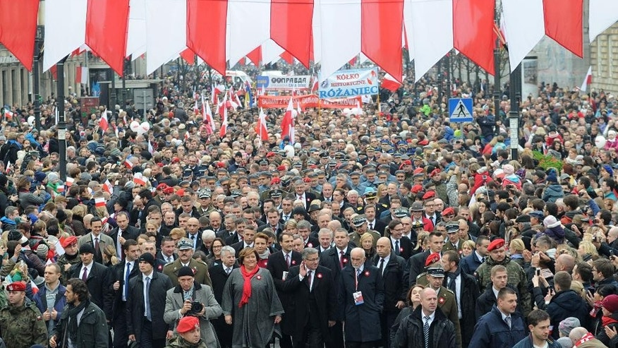 Polish President Bronislaw Komorowski, first row center, leads a march along downtown streets to mark the 96th anniversary of Poland's independence in Warsaw, Poland, Tuesday, Nov. 11, 2014. (AP Photo/Alik Keplicz)