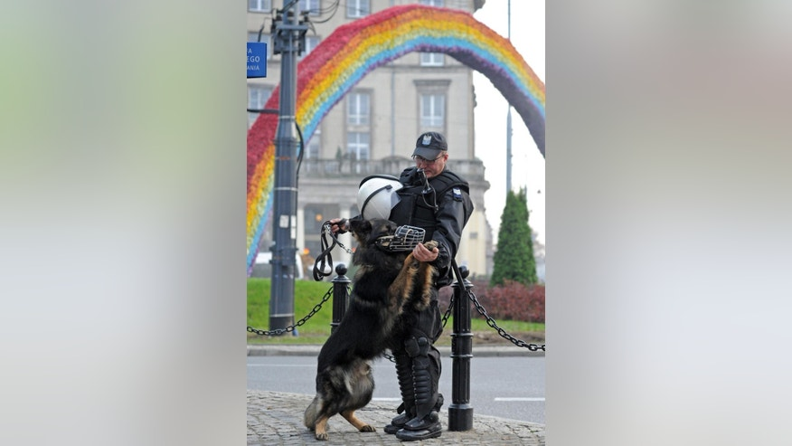 A riot police officer plays with his dog as he guards a controversial art installation, the Rainbow, which was burnt  during previous Independence Day celebrations by right wing activists,  in Warsaw, Poland, Tuesday, Nov. 11, 2014, on the 96th anniversary of the country's independence. (AP Photo/Alik Keplicz)