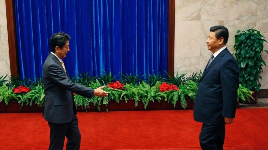 Japan's Prime Minister Shinzo Abe, left, and China's President Xi Jinping, prepare to shake hands during their meeting at the Great Hall of the People, on the sidelines of the Asia-Pacific Economic Cooperation (APEC) summit, in Beijing, Monday, Nov. 10, 2014. An uneasy handshake Monday between Xi and Abe marked the first meeting between the two men since either took power, and an awkward first gesture toward easing two years of high tensions. (AP Photo/Kim Kyung-Hoon, Pool)