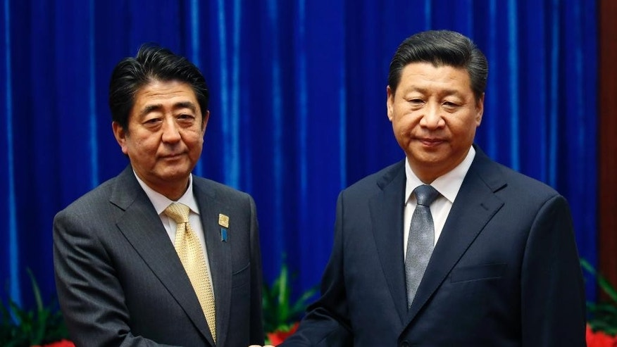 Japan's Prime Minister Shinzo Abe, left, and China's President Xi Jinping, right, shake hands during their meeting at the Great Hall of the People, on the sidelines of the Asia-Pacific Economic Cooperation (APEC) summit, in Beijing, Monday, Nov. 10, 2014. An uneasy handshake Monday between Xi and Abe marked the first meeting between the two men since either took power, and an awkward first gesture toward easing two years of high tensions. (AP Photo/Kim Kyung-Hoon, Pool)