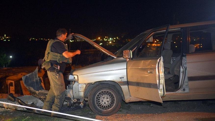 An Israeli soldier inspects a vehicle at the scene of an attack near the West Bank Jewish settlement of Alon Shvut Monday, Nov. 10, 2014. Palestinian assailants on Monday carried out a pair of stabbing attacks in Tel Aviv and the West Bank, police said, killing an Israeli teenage girl and gravely wounding a soldier as a wave of Arab unrest appeared to be gaining strength. (AP Photo/Mahmoud Illean)
