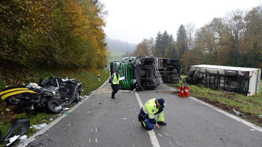 Police investigate the course of action after a car crash in Lengnau near Biel, Switzerland, Tuesday morning Nov. 11, 2014. Swiss police said several people are dead or injured in a severe crash involving a truck, a Swiss postal bus and a car in northern Switzerland.  (AP Photo/Keystone, Steffen Schmidt)