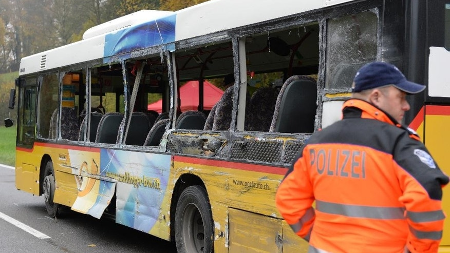 A police officer stands beside a damaged bus in Lengnau near Biel, Switzerland, Tuesday morning Nov. 11, 2014. Swiss police said several people are dead or injured in a severe crash involving a truck, a Swiss postal bus and a car in northern Switzerland.  (AP Photo/Keystone, Steffen Schmidt)