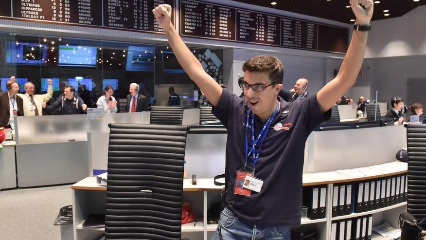 The picture released by the European Space Agency ESA on Wednesday, Nov. 12, 2014, a scientist reacts in the main control room at the European Space Agency after the first unmanned spacecraft Philae landed on the comet called 67P/Churyumov-Gerasimenko, at the control centre in Darmstadt, Germany, Wednesday, Nov. 12, 2014. Europe's Rosetta space probe was launched in 2004 with the aim of studying the comet and learning more about the origins of the universe. (AP Photo/ESA, J.Mai)
