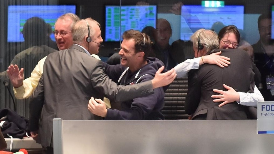 The picture released by the European Space Agency ESA on Wednesday, Nov. 12, 2014, showing scientists as they react in the main control room at the ESA after the first unmanned spacecraft Philae landed on the comet called 67P/Churyumov-Gerasimenko, at the control centre in Darmstadt, Germany, Wednesday, Nov. 12, 2014. Europe's Rosetta space probe was launched in 2004 with the aim of studying the comet and learning more about the origins of the universe. (AP Photo/ESA, J.Mai)