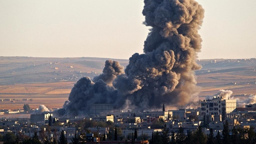 Nov. 8, 2014: Smoke rises from an Islamic State position in eastern Kobani, after an airstrike by the US led coalition, seen from a hilltop outside Suruc, on the Turkey-Syria border Saturday . Kobani, also known as Ayn Arab, and its surrounding areas, has been under assault by extremists of the Islamic State group since mid-September and is being defended by Kurdish fighters.