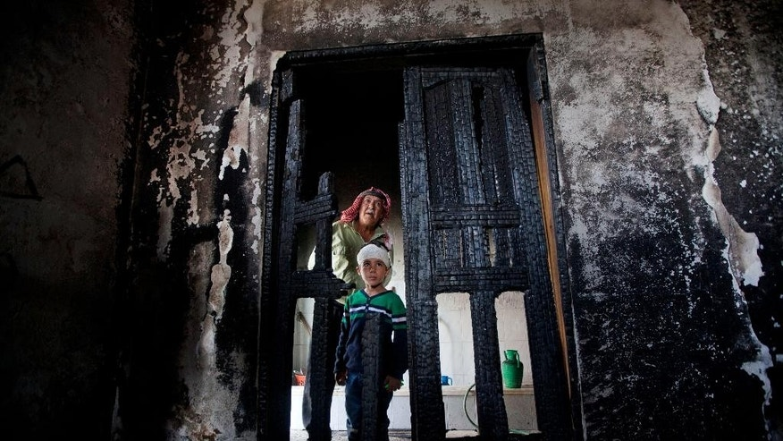 Palestinians inspect damages of a mosque following an attack in the West Bank village of Mughayer, north of Ramallah, Wednesday, Nov. 12, 2014. An attack against a mosque in a West Bank village early on Wednesday ignited a fire that destroyed its first floor, the village's mayor said, blaming Jewish settlers for the attack.(AP Photo/Majdi Mohammed)