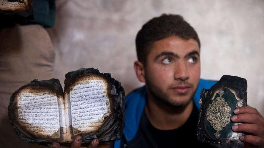 A Palestinian shows a damaged Quran, Islam's holy book, in a mosque following an attack in the West Bank village of Mughayer, north of Ramallah, Wednesday, Nov. 12, 2014. An attack against a mosque in a West Bank village early on Wednesday ignited a fire that destroyed its first floor, the village's mayor said, blaming Jewish settlers for the attack. (AP Photo/Majdi Mohammed)