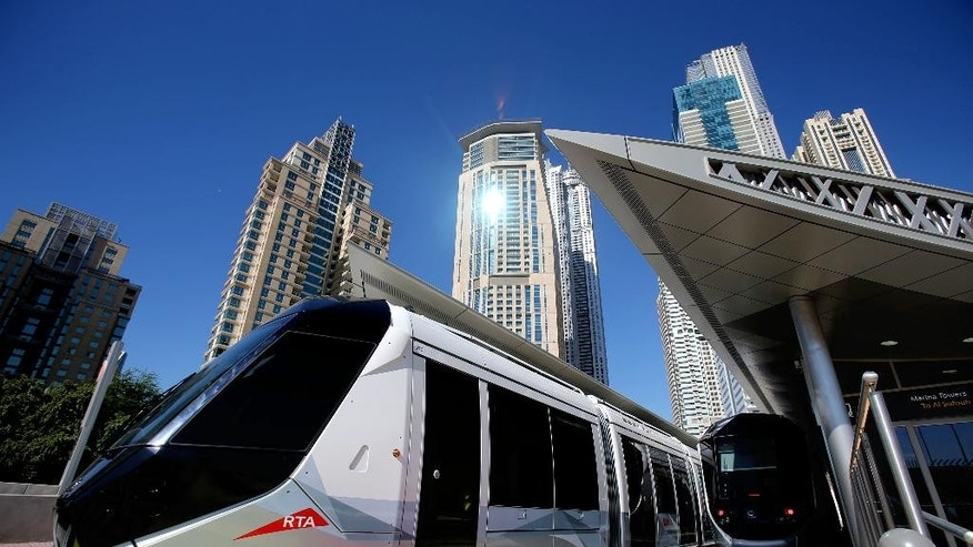 A tram leaves Marina Towers station during the first day of operation in Dubai, United Arab Emirates, Wednesday, Nov. 12, 2014. The car-loving Mideast commercial hub of Dubai has opened its first tram line, enticing would-be riders with air-conditioned stations and a premium section on its sleek cars for big-spending commuters. (AP Photo/Kamran Jebreili)